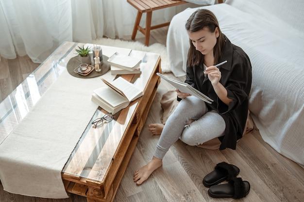Uma jovem aluna faz tarefas em casa, sentada com um caderno nas mãos.