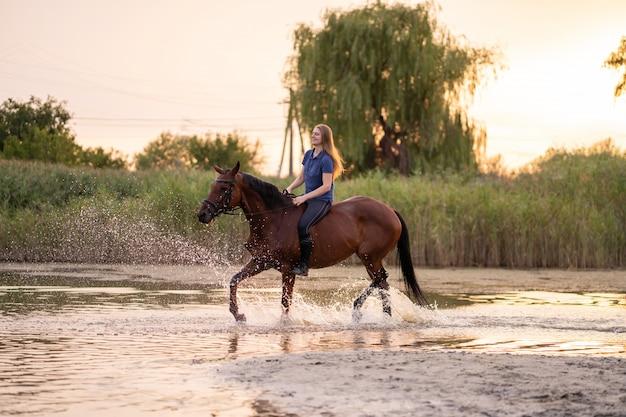Uma jovem andando a cavalo em um lago raso,