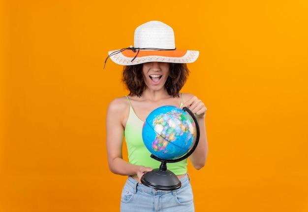 Uma jovem animada, com cabelo curto, com top verde e chapéu de sol, olhando para um globo e sorrindo