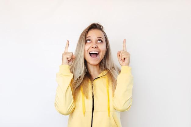 Uma jovem aponta para copiar o espaço vazio para texto ou desenho com dois dedos apresentando o produto