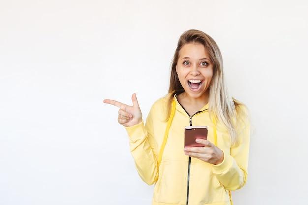 Uma jovem aponta uma cópia do espaço vazio para um texto ou desenho com o dedo segurando um telefone celular