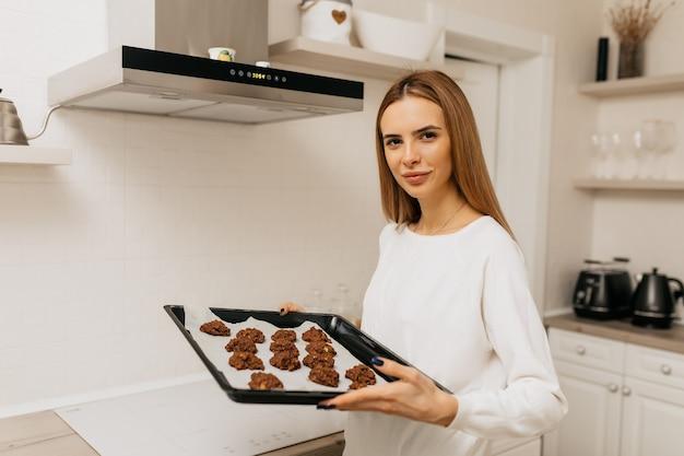 Uma jovem aprende a cozinhar e segurando deco com biscoitos caseiros