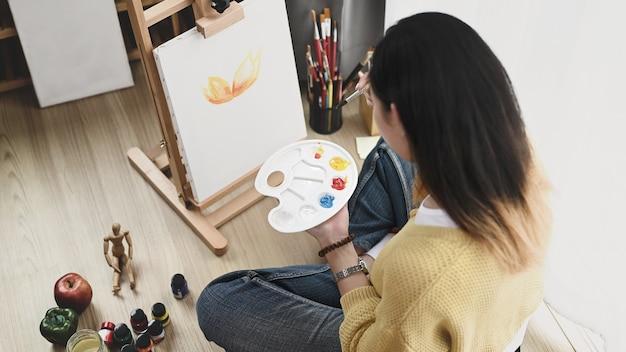 Uma jovem artista com uma paleta na mão, pintando na tela, enquanto está sentada no chão de sua oficina.