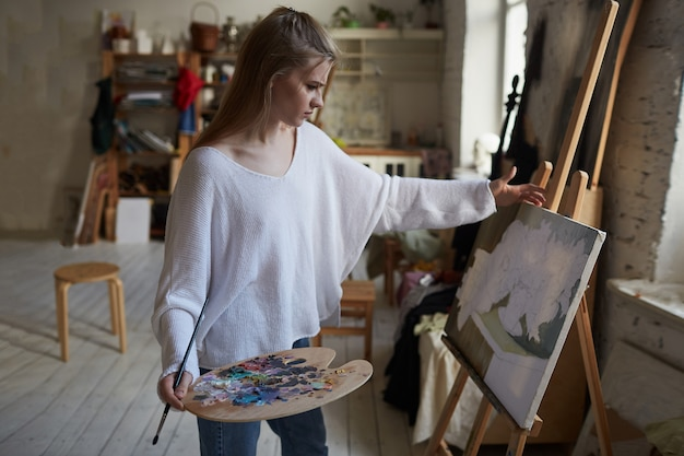 Uma jovem artista cria seus primeiros esboços com um pincel sobre tela