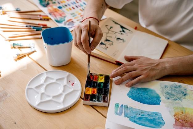 Uma jovem artista desenha em um caderno enquanto está sentado em uma mesa de madeira. lindas mãos masculinas estão segurando um lápis de cor. fechar-se. raios de sol e ambiente agradável. conceito diy. criador de arte real em ação