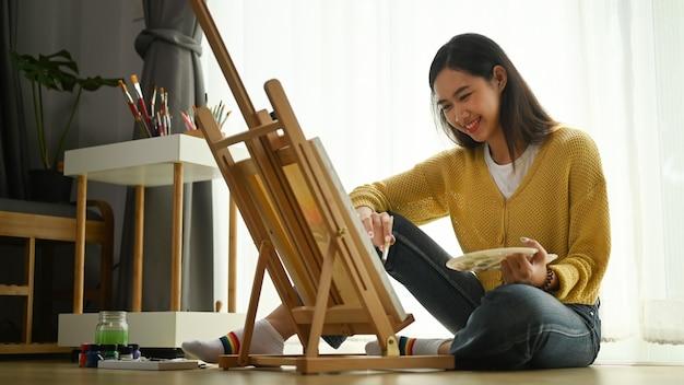 Uma jovem artista feminina de suéter amarelo com paleta na mão está pintando sobre tela no chão.