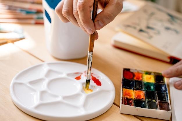 Uma jovem artista pinta com aquarela em um caderno sentado em uma mesa de madeira.