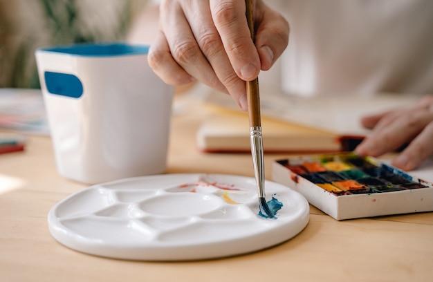 Uma jovem artista pinta com aquarelas em um caderno sentado a uma mesa de madeira. lindas mãos masculinas estão segurando uma escova. fechar-se. raios de sol e ambiente agradável. conceito de artesanato. o artista em ação