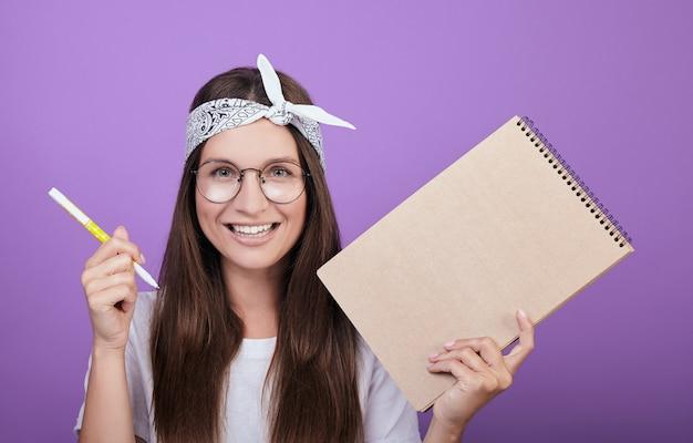 Uma jovem artista segura um álbum e uma caneta nas mãos.