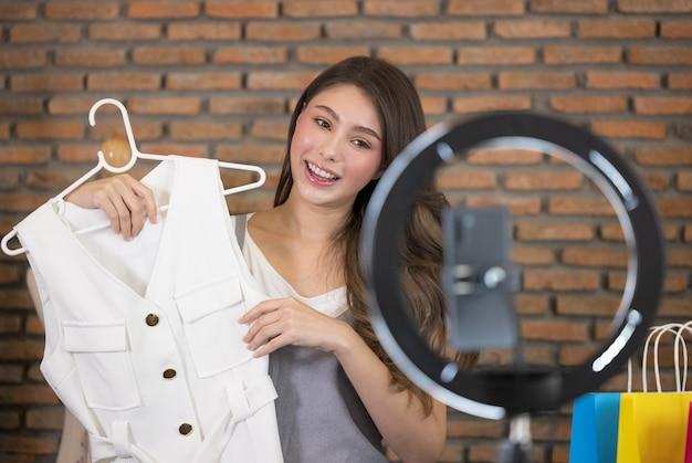 Uma jovem asiática ao vivo para venda de roupas de moda é uma blogueira apresentando-se para pessoas sociais. ela é influenciadora em redes sociais online.