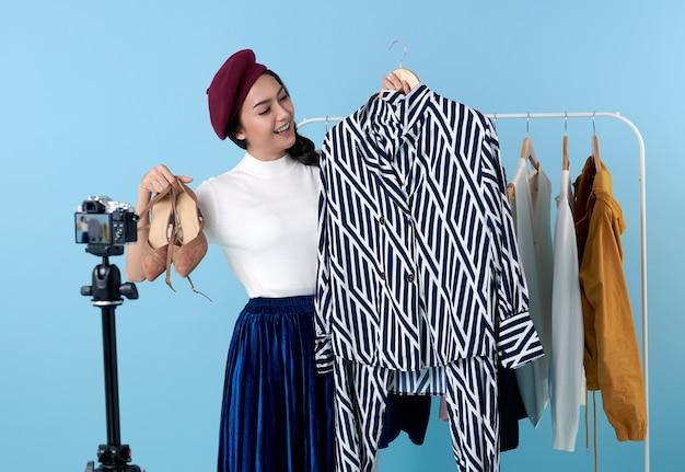 Uma jovem asiática ao vivo que vende roupas de moda é uma blogueira que se apresenta para pessoas sociais. seu influenciador nas redes sociais online.