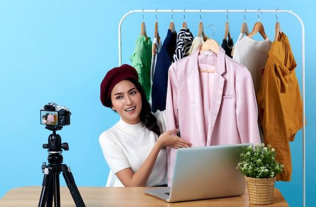 Uma jovem asiática ao vivo que vende roupas de moda é uma blogueira que se apresenta para pessoas sociais. seu influenciador nas redes sociais online