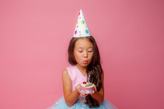 Uma jovem asiática apaga uma vela em uma rosa em uma festa de aniversário