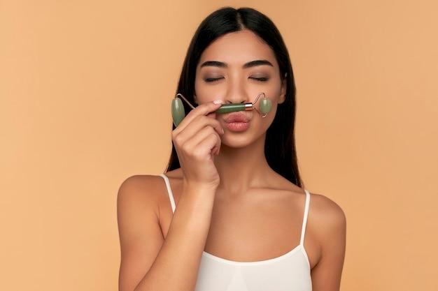 Uma jovem asiática com pele limpa e radiante faz massagem facial com rolo de quartzo em bege