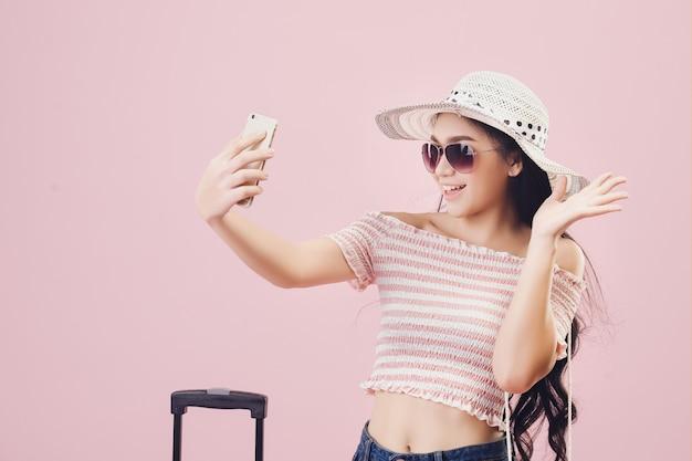 Uma jovem asiática com um rosto brilhante, usando um chapéu e usando óculos está tirando uma selfie em fundo rosa de estúdio. filtros de tom rosa pastel.