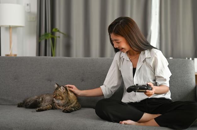 Uma jovem asiática está sentada no sofá com seu gato e segurando um console, jogando