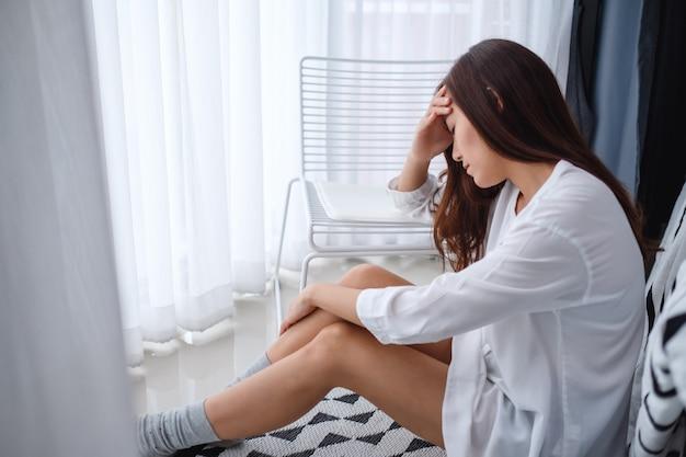 Uma jovem asiática triste e estressada, sentada sozinha no quarto