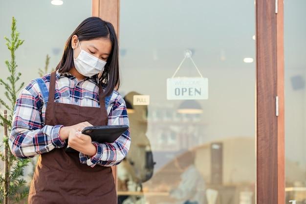 Uma jovem assistindo o tempo no tablet antes do café aberto e tem uma placa que diz bem-vindo, estamos abertos