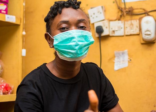 Uma jovem atendente africana fica feliz ao usar sua máscara facial para evitar o surto de corona e fez sinal de positivo