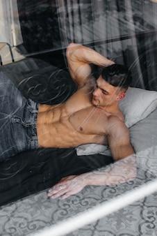 Uma jovem atleta sexy com abs perfeito deita-se na cama no estúdio em jeans ao fundo em topless. estilo de vida saudável, alimentação adequada, programas de treinamento e nutrição para perda de peso.