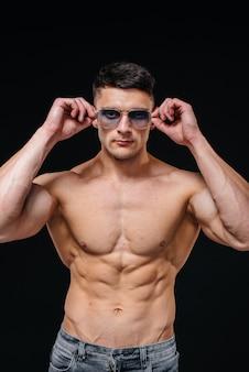 Uma jovem atleta sexy com abs perfeito posa no estúdio em topless em jeans e um par de óculos de proteção. estilo de vida saudável, alimentação adequada, programas de treinamento e nutrição para perda de peso.