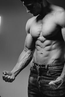Uma jovem atleta sexy com abs perfeito posa no estúdio em topless em jeans. estilo de vida saudável, alimentação adequada, programas de treinamento e nutrição para perda de peso. preto e branco.