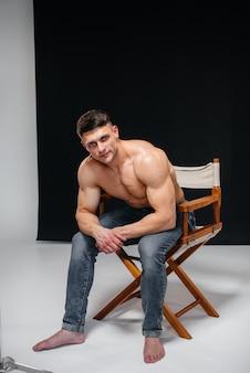 Uma jovem atleta sexy com abs perfeito posa no estúdio em topless em jeans no fundo. estilo de vida saudável, alimentação adequada, programas de treinamento e nutrição para perda de peso.
