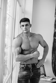 Uma jovem atleta sexy com abs perfeito posa perto da janela no estúdio em topless em jeans. estilo de vida saudável, alimentação adequada, programas de treinamento e nutrição para perda de peso. preto e branco.