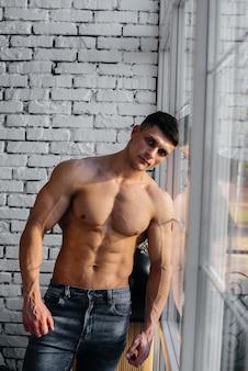 Uma jovem atleta sexy com abs perfeito posa perto da janela no estúdio em topless em jeans no fundo. estilo de vida saudável, alimentação adequada, programas de treinamento e nutrição para perda de peso.