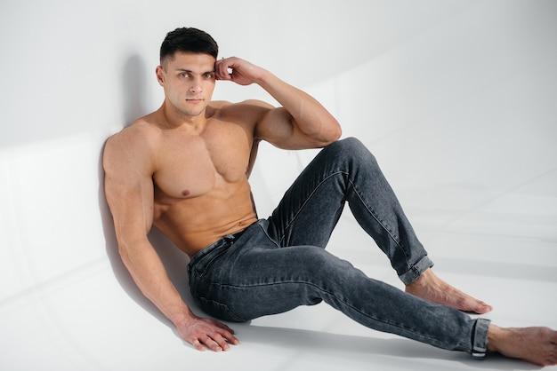 Uma jovem atleta sexy com abs perfeito senta-se no chão do estúdio em topless em jeans ao fundo. estilo de vida saudável, alimentação adequada, programas de treinamento e nutrição para perda de peso.