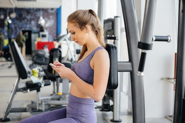 Uma jovem atleta usa seu telefone na academia e tira uma selfie.