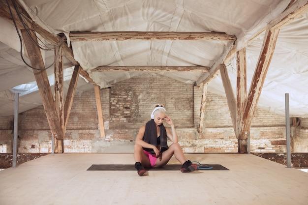 Uma jovem atlética com fones de ouvido brancos malhando ouvindo música em uma construção abandonada