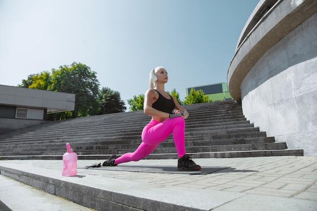 Uma jovem atlética em camisa e fones de ouvido brancos malhando ouvindo música na rua ao ar livre. fazendo estocadas e alongamentos. conceito de estilo de vida saudável, esporte, atividade, perda de peso.