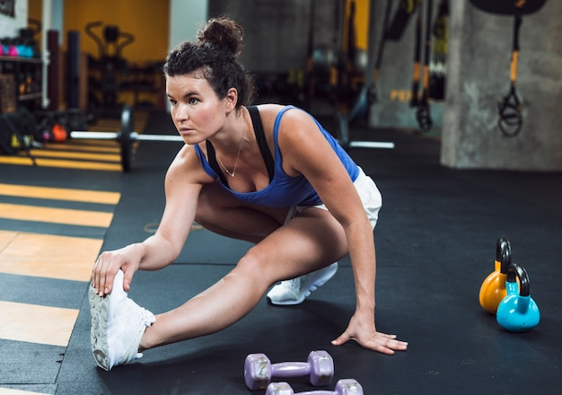 Uma jovem atlética, esticando a perna no clube de fitness