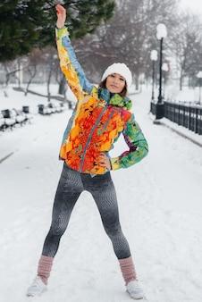 Uma jovem atlética pratica esportes em um dia gelado e com neve. fitness, corrida.