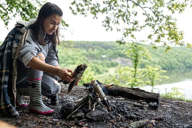 Uma jovem atraente acende uma fogueira para se aquecer na floresta.