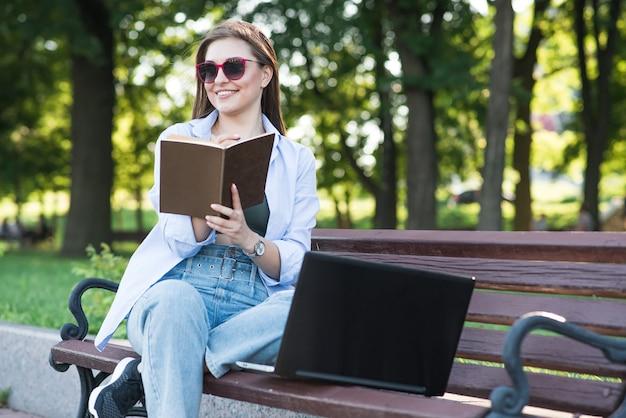 Uma jovem atraente caucasiana, sentado em um banco do parque e escrevendo em um caderno. freelancer, estudante. conceito de educação