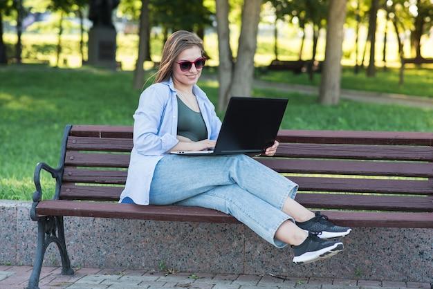 Uma jovem atraente caucasiana, sentado em um banco do parque e usando um laptop. freelancer, estudante. conceito de rede