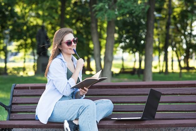 Uma jovem atraente caucasiana sentado em um banco do parque, segurando um bloco de notas e pensando. freelancer, estudante. conceito de educação