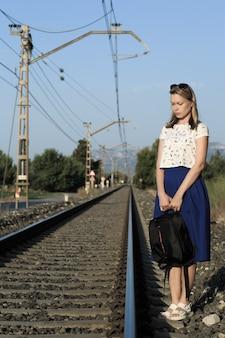 Uma jovem atraente, com longos cabelos castanhos, caminhando perto da ferrovia.