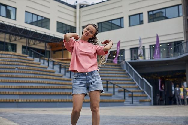 Uma jovem atraente com tranças na cidade a pé perto do moderno centro de negócios de alta qualidade ...