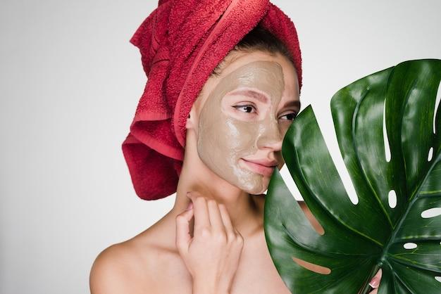 Uma jovem atraente com uma toalha vermelha na cabeça aplicou uma máscara de argila em metade do rosto