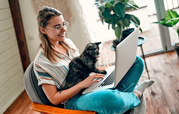 Uma jovem atraente de óculos está trabalhando em um laptop enquanto está sentado de pernas cruzadas em uma cadeira confortável em casa com um gato assistente engraçado nas pernas.