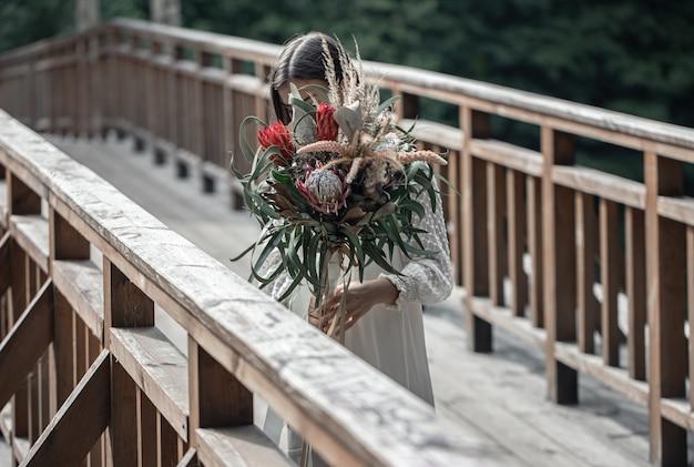 Uma jovem atraente em uma ponte de madeira está com um buquê de flores exóticas.