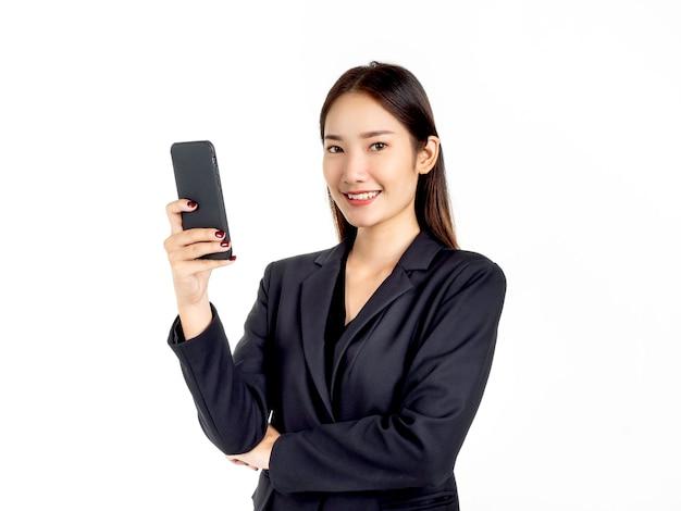 Uma jovem atraente empresária asiática de terno usando smartphone e olhando a câmera
