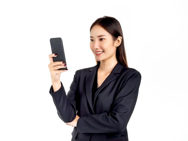 Uma jovem atraente empresária asiática de terno usando smartphone, olhando na tela