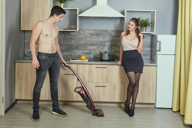 Uma jovem atraente está flertando com um homem branco sem camisa, que está limpando a cozinha usando uma vassoura elétrica sem fio.