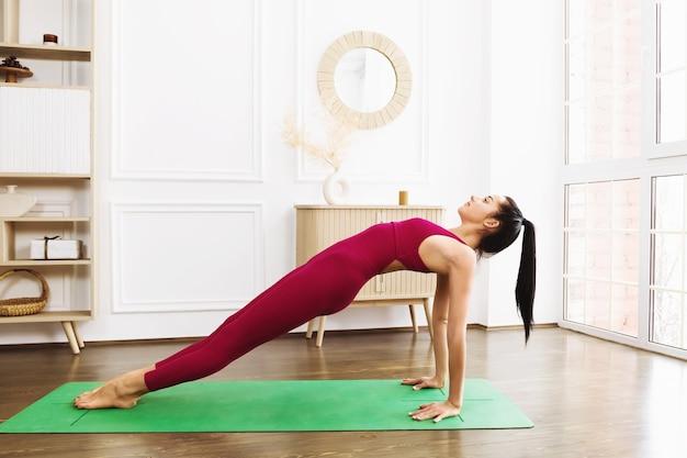 Uma jovem atraente praticando ioga em uma barra invertida e fazendo uma pose de purvottanasana usando roupas esportivas cor de rosa em um quarto
