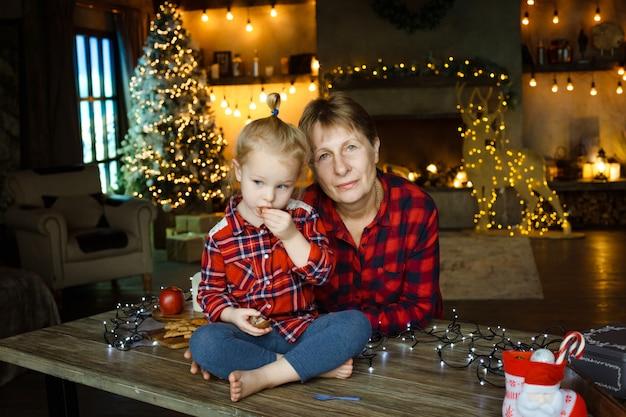 Uma jovem avó com sua pequena neta que se senta em uma mesa e come doces de um presente de natal.