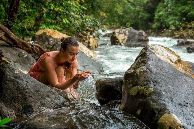 Uma jovem bebe água de um riacho na montanha